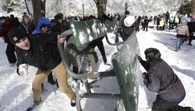 People taking part in a public snowball fight use a table as shield at Wright Park