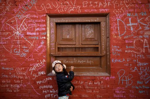 A girl looks towards her father as she writes on the wall of a temple