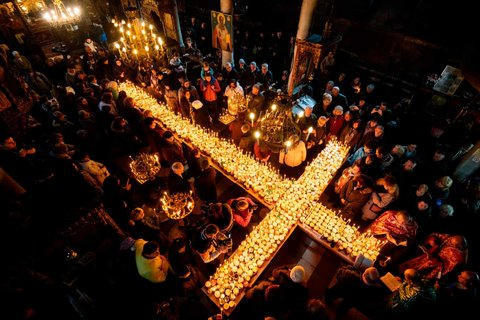 People pray around a cross-shaped platform covered with candles in jars of honey during a ceremony marking the day of Saint Haralampi, protector of beekeepers, at the Church of the Blessed Virgin