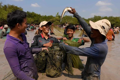 A man holds up a snake fish during a ceremony at Choam Krovean commune