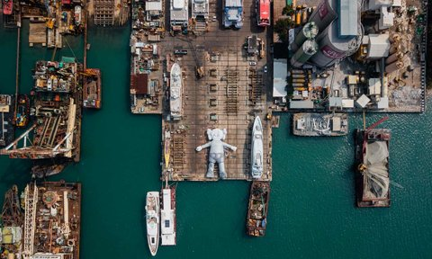 A 121-foot-long inflatable installation of American contemporary artist Brian Donnelly's famous Companion seen at rest in a shipyard . The figure is part of a project, titled KAWS:HOLIDAY, and is part of Art Basel, Hong Kong.